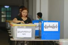 A woman places her ballot into the Pyithu Hluttaw representative election box in the April 2012 by-elections.